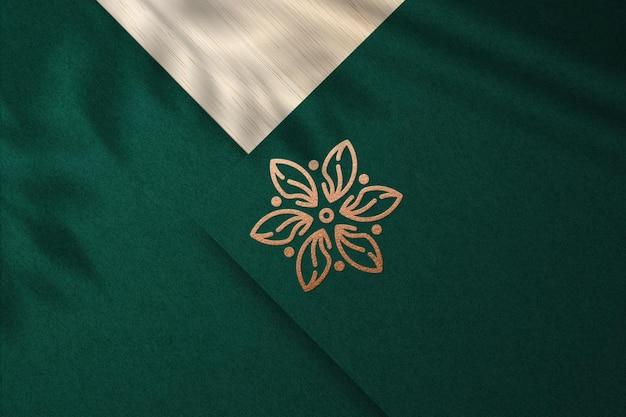 Mockup realistico con logo in rilievo con lamina di bronzo su carta verde
