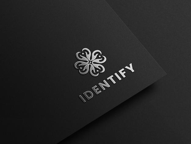 Mockup realistico del logo in lamina d'argento su carta nera con effetti in rilievo
