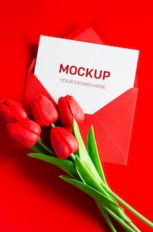 Busta rossa con carta bianca vuota e bouquet di tulipani.