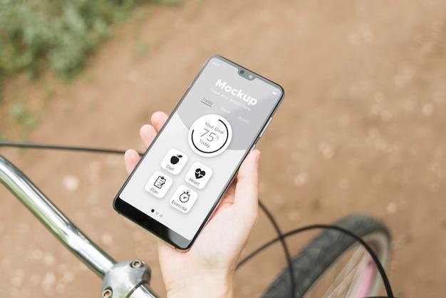 In sella alla bici e utilizzando un modello digitale dello smartphone