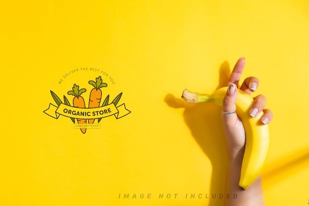 Banane fresche mature frutta in mano di una donna con mockup