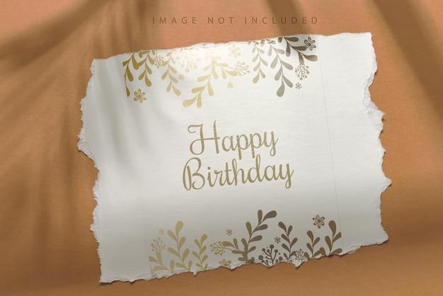 Carta di compleanno hapy bianco strappato con ombra sul marrone