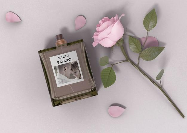 Rosa accanto alla bottiglia di profumo sul tavolo