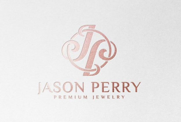 Mockup di logo in lamina d'oro rosa su carta ruvida bianca
