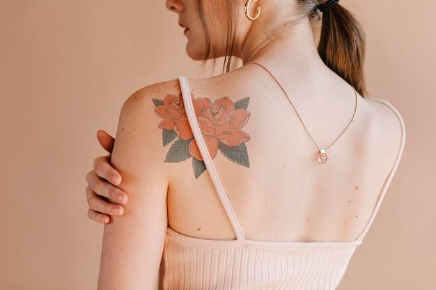 Mockup di disegno del tatuaggio rosa psd sulla spalla di una donna