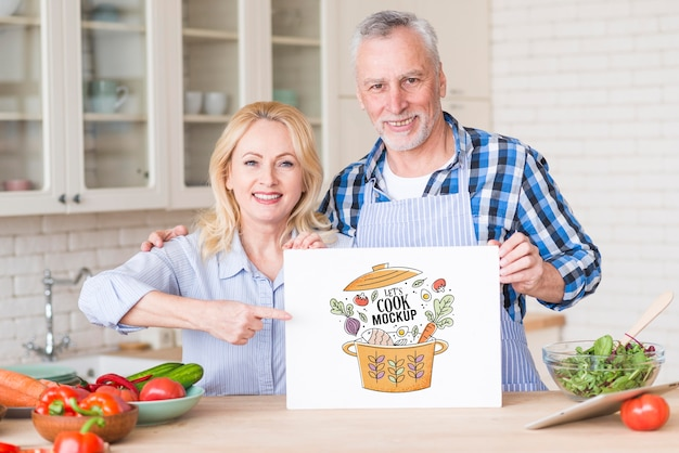 Coppia senior in cucina tenendo la carta mock-up Psd Premium