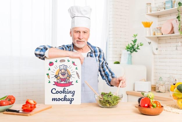 Uomo anziano in cucina tenendo la carta mock-up