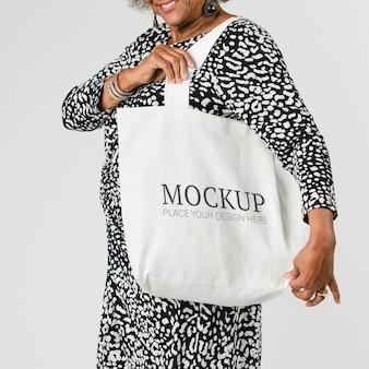 Donna anziana che tiene un modello di borsa tote