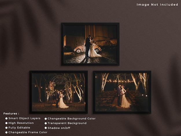 Set di mockup di cornice per foto orizzontale nera appeso sullo sfondo della parete con ombra.