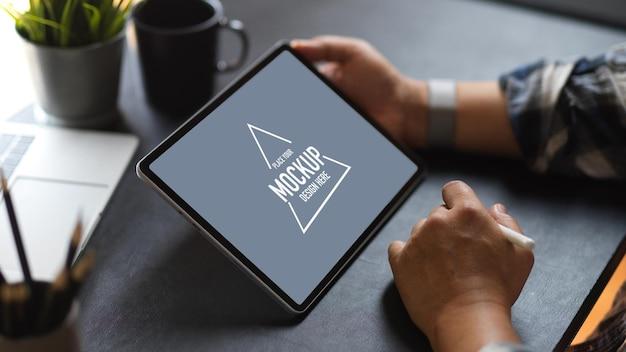 Vista laterale dell'uomo d'affari utilizzando lo schermo di mockup della tavoletta digitale sullo spazio di lavoro scuro