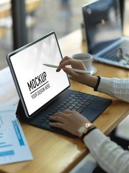 Vista laterale della donna di affari che lavora con il modello di tavoletta digitale