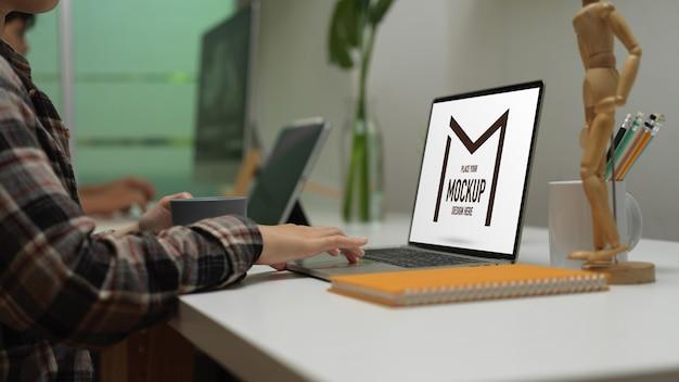 Vista laterale dell'impiegato femminile che lavora con mock up laptop sul tavolo da lavoro nella stanza dell'ufficio