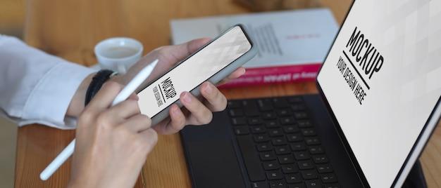 Vista laterale della donna utilizza lo smartphone mentre si lavora con il mockup tablet