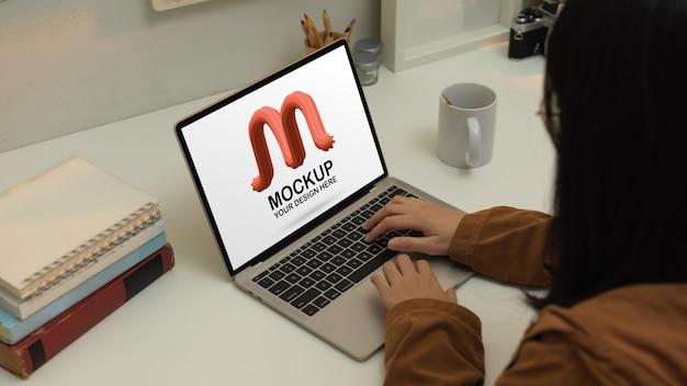Vista laterale della donna che lavora con il laptop mockup sulla scrivania dell'ufficio domestico