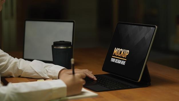 Vista laterale della scrittura femminile sul mockup del notebook mentre si lavora con il tablet
