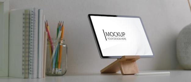 Vista laterale della scrivania dell'home office con mock up tablet, cancelleria e copia spazio