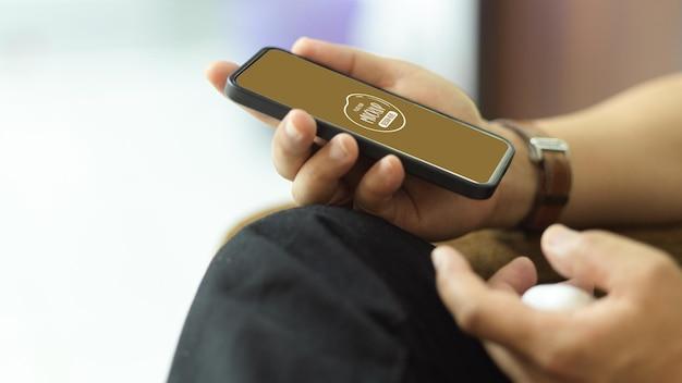 Vista laterale della mano maschio che tiene il modello di smartphone
