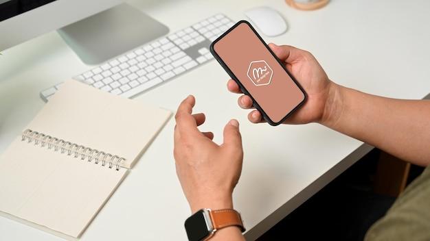 Vista laterale della mano maschio che tiene smartphone