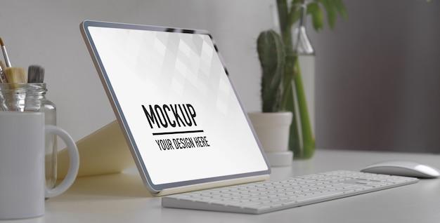 Vista laterale del piano di lavoro con mock up tablet e forniture per ufficio