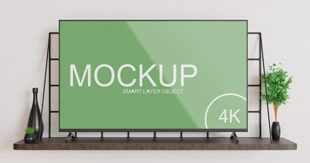 Mockup di smart tv in piedi sul tavolo a muro in legno