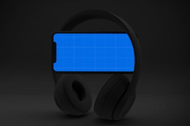 Smartphone con schermo e cuffie del modello, concetto di musica di app