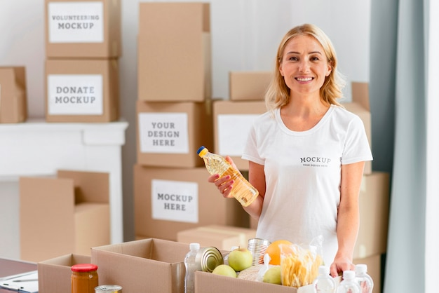 Volontario femminile di smiley che tiene le disposizioni prima di metterle nella scatola