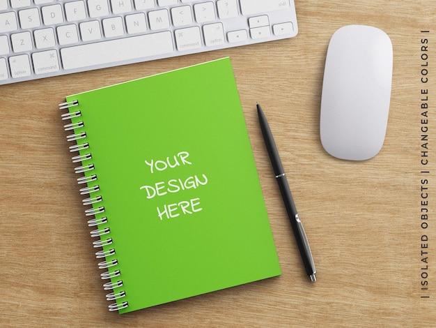 Modello di copertina rigida del pianificatore del diario del taccuino a spirale con il concetto del lavoro d'ufficio della penna sulla tavola di legno isolata