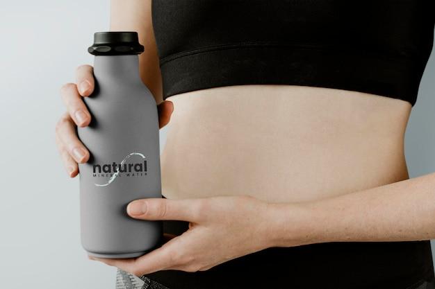 Donna sportiva con un modello di bottiglia d'acqua