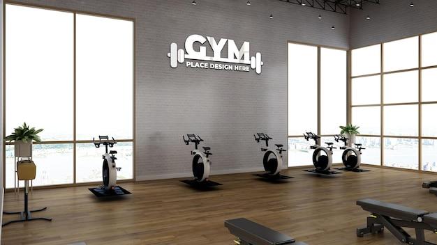 Modello di logo sportivo nella sala fitness con parete bianca