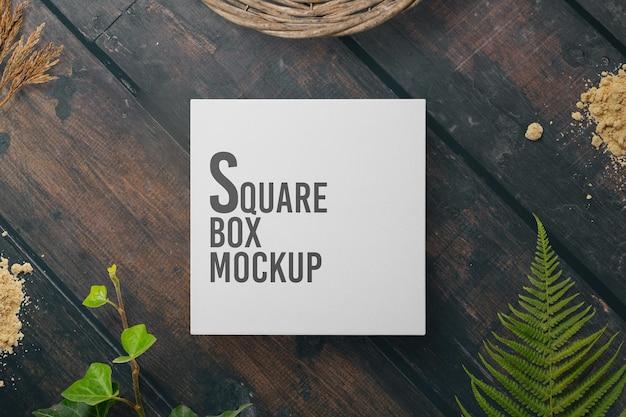 Design mockup scatola quadrata sul tavolo di legno