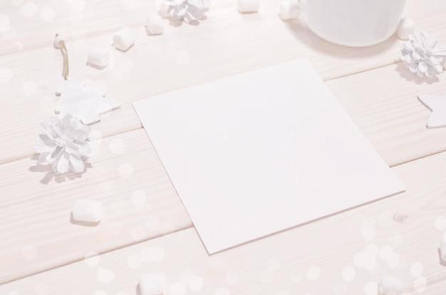 Mockup di carta quadrata con decorazioni bianche sul tavolo di legno