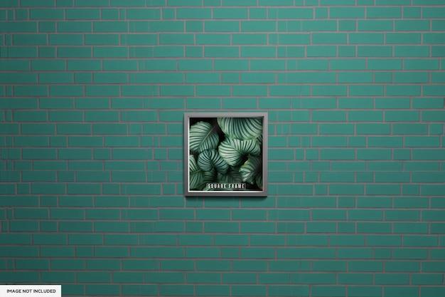 Mockup di foto con cornice quadrata con poster con cornice verde wallf con muro verde