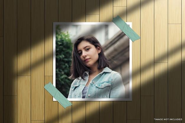 Mockup fotografico con cornice di carta quadrata con sovrapposizione di ombre della finestra e sfondo in legno