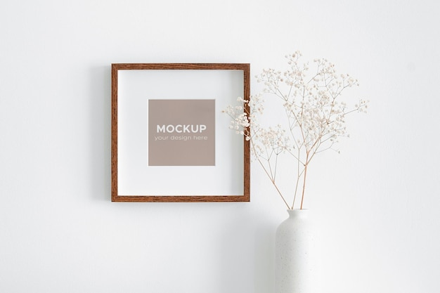 Mockup di cornice quadrata su muro bianco con decorazioni di piante di gypsophila a secco