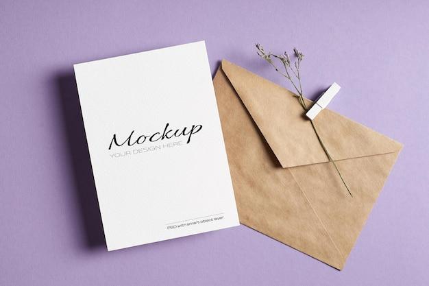 Mockup di biglietto di auguri stazionario con busta e ramoscello di fiori secchi