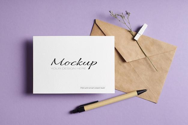 Mockup di biglietto di auguri stazionario con busta, penna e ramoscello di fiori secchi