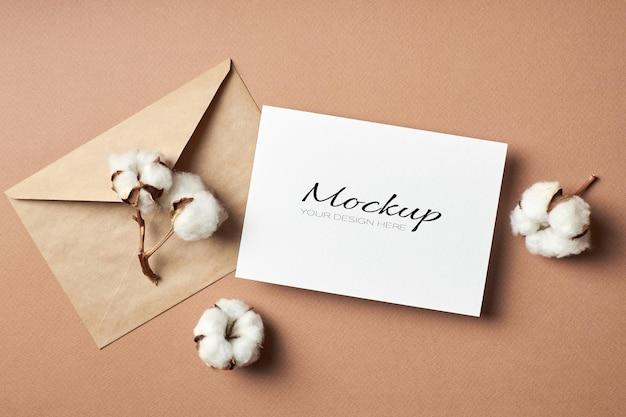 Invito stazionario o mockup di biglietto di auguri con busta e fiori di piante di cotone naturale