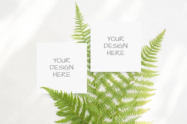 Mockup di cancelleria con felci verdi su uno spazio bianco in stile minimalista