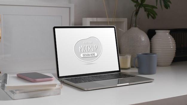 Tavolo da studio con mock up di laptop, smartphone, libri, cancelleria e decorazioni