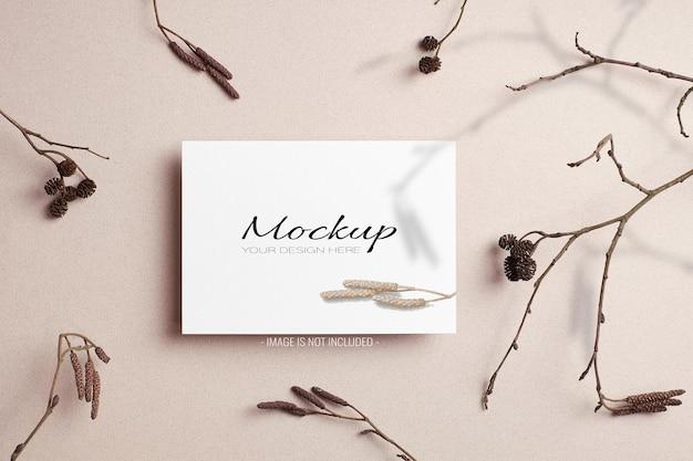 Elegante mockup sazionario di invito o biglietto di auguri con decorazioni di ramoscelli di albero secco e ombra