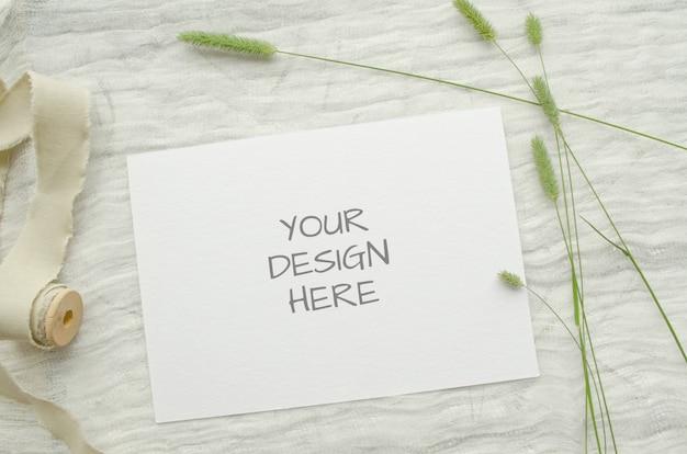 Ard di mockup di cartoleria estiva per biglietto di auguri o invito a nozze con erbe, bobina vintage di treccia di cotone, su uno spazio leggero.