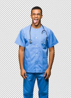 Chirurgo medico uomo che mostra la lingua alla telecamera con sguardo divertente
