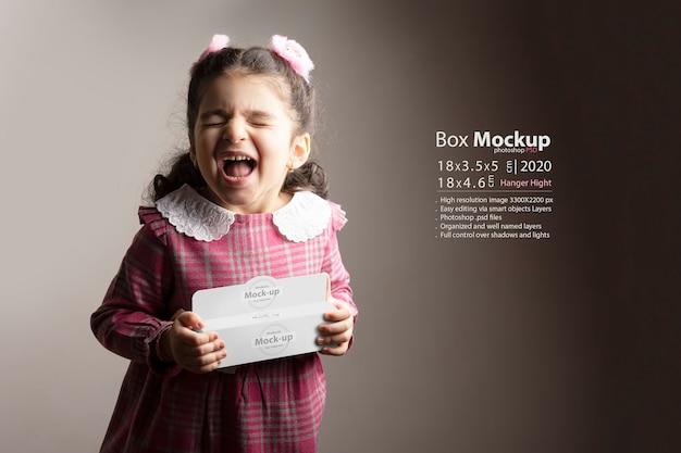 Bambina sorpresa che tiene una piccola confezione regalo a portata di mano