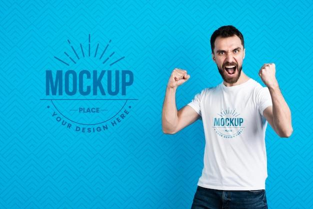 Uomo di mock-up di t-shirt che mostra il gesto di vittoria
