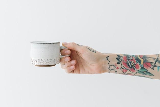 Mano tatuata che tiene un modello di tazza di caffè bianco