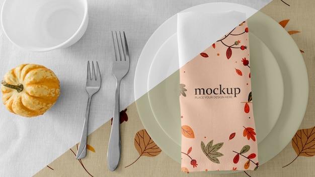 Disposizione dei tavoli da pranzo del ringraziamento con tovagliolo sul piatto e zucca