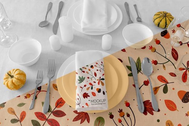 Disposizione dei tavoli da pranzo del ringraziamento con tovagliolo su piatti e posate