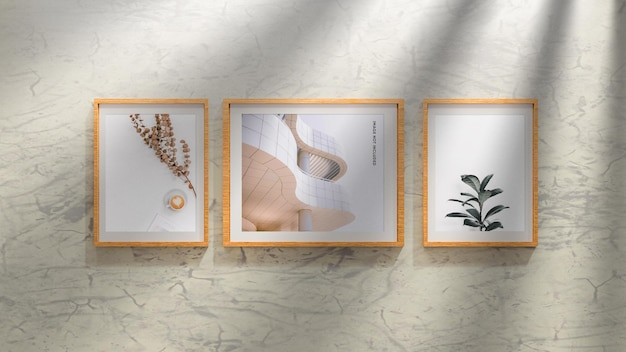 Mockup di tre cornici per foto in legno sul muro