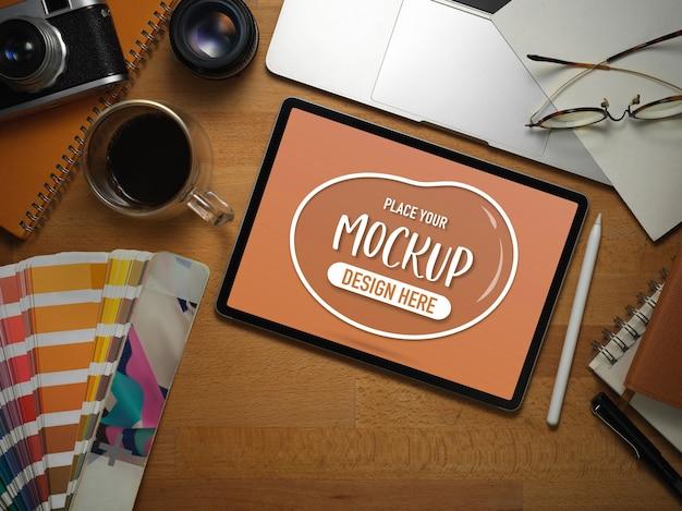 Vista dall'alto dell'area di lavoro dell'artista con mock up tablet, laptop, campione di colore e forniture