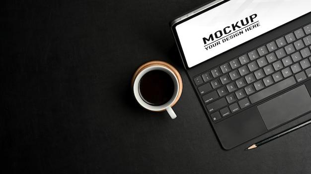 Vista dall'alto del mockup di tavoletta digitale dell'area di lavoro di concetto nero, tastiera e tazza di caffè